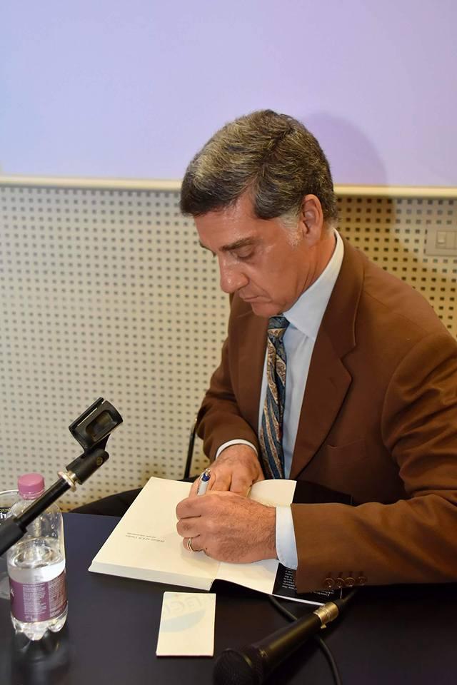 Marco Tullio Barboni mentre firma autografi