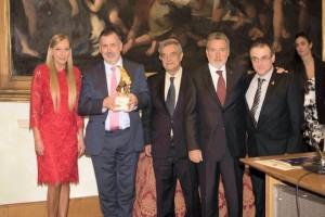 Da sinistra: l'addetta stampa del Premio Gisella Peana consegna il Premio al Direttore della British School di Roma Prof. Stephen Milner, che riceve il Premio per l'archeologo Cyprian Broodbank, insieme allo scrittore Dante Maffia,  al  presidente Dr. Carlo Sgandurra e allo scultore Alessandro Marrone